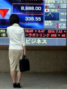 TOKYO, JAPAN - OCTOBER 7:  An unidentified woman stands in front of stock board on October 7, 2002 in Tokyo, Japan. The average has fallen by 39.55 points or 3.76% and closed at 8,688.00.  (Photo by Koichi Kamoshida/Getty Images).